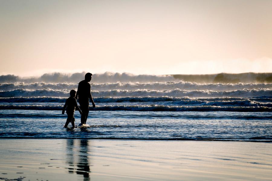 フリー写真 海の浅瀬を歩く父親と息子