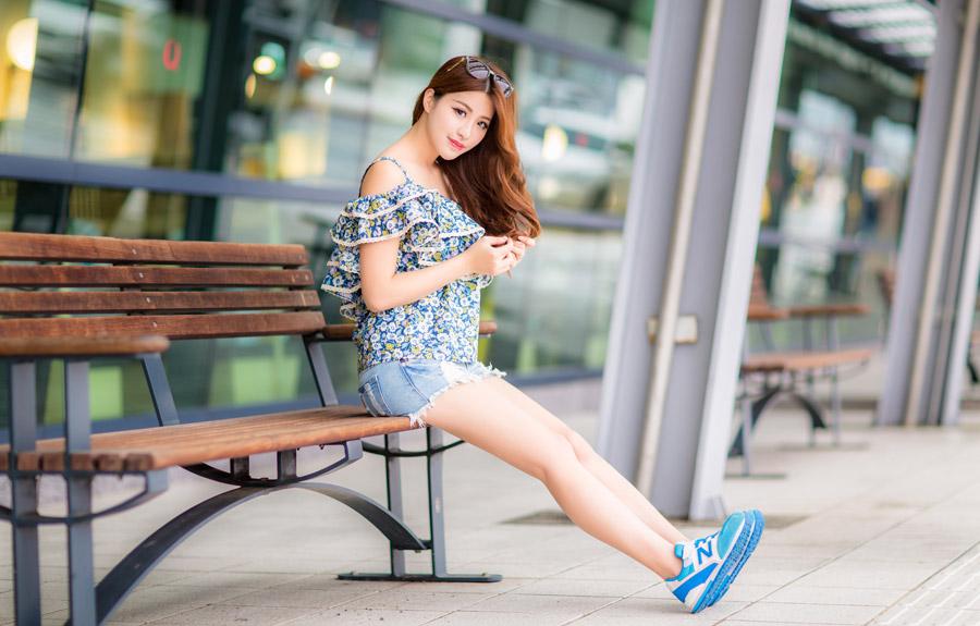 フリー写真 ベンチに足を伸ばして座る女性ポートレイト