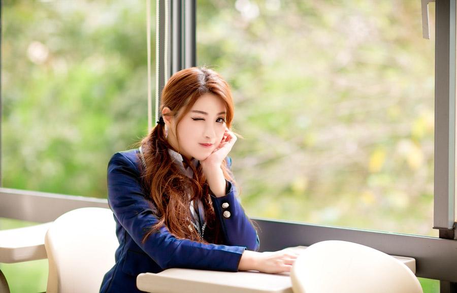 フリー写真 窓際の席に着きながらウインクしている女子高生