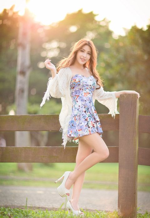 フリー写真 柵に手をついて片足を上げる女性