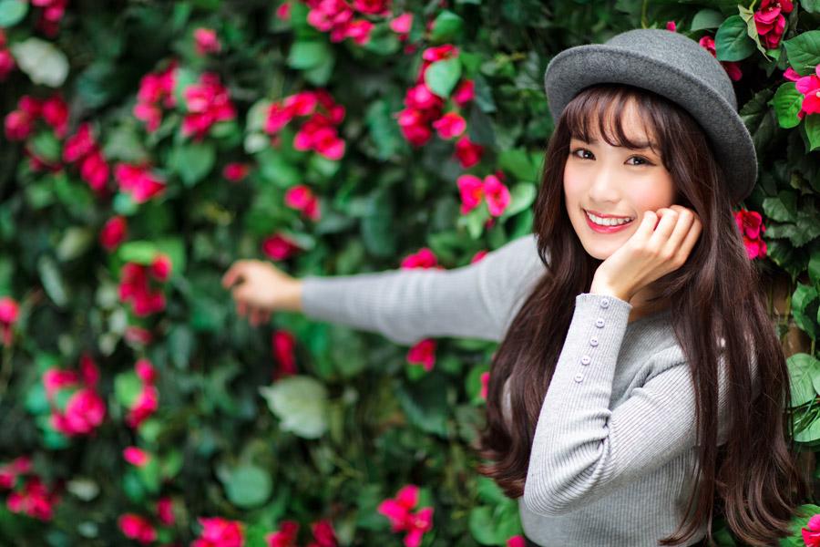 フリー写真 花の前で頬に手を当てる女性のポートレイト