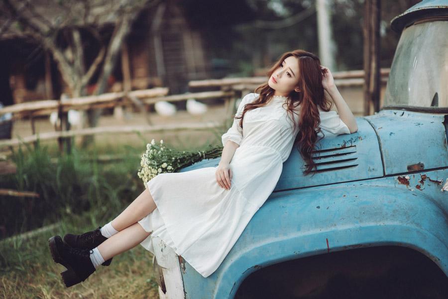 フリー写真 放置された車の上に寝転ぶ女性のポートレイト
