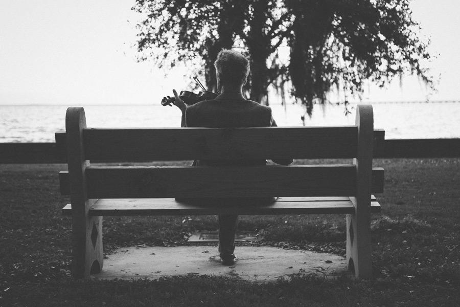 フリー写真 ベンチでバイオリンを弾く中年男性の後ろ姿