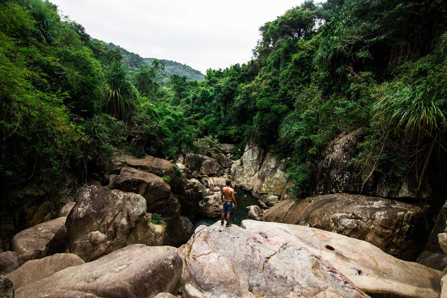 フリー写真 渓谷の岩の上に立つ男性の後ろ姿