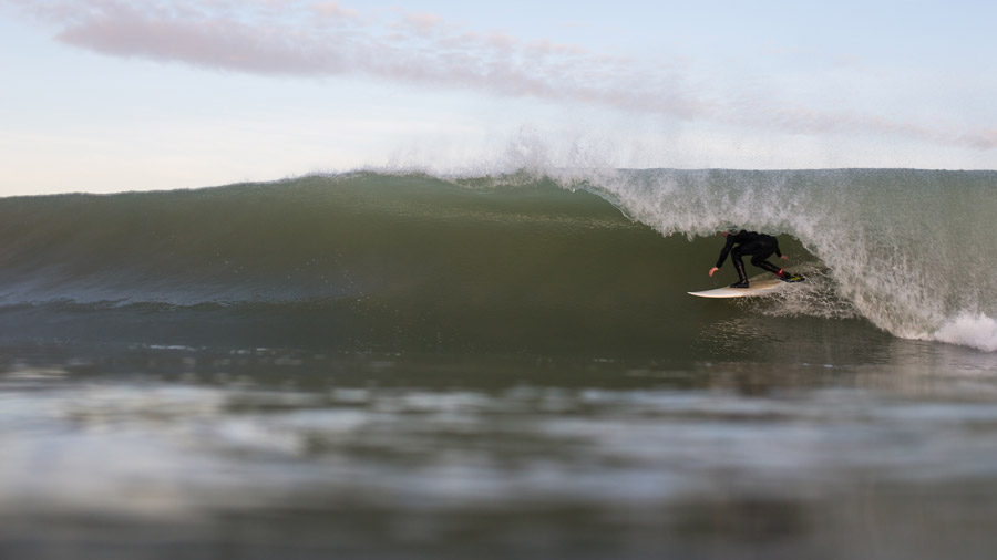 フリー写真 波のトンネルをくぐるサーファー