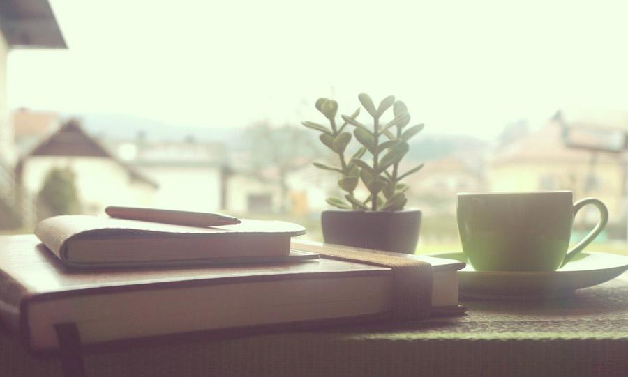 フリー写真 窓辺に置かれたコーヒーカップと手帳