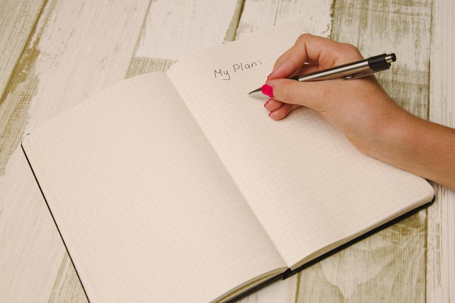 フリー写真 手帳にプランを書く手