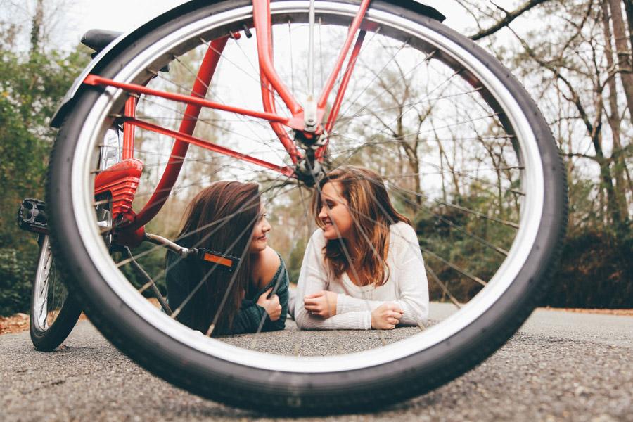フリー写真 自転車と腹這い姿で見つめ合う二人の女性