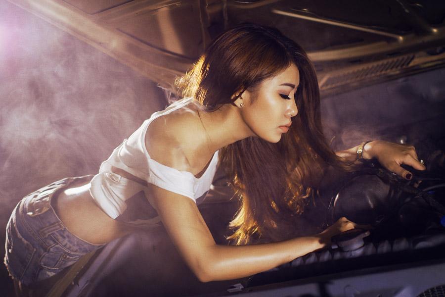 フリー写真 ボンネットを開けて車を整備する女性