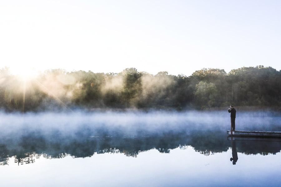 フリー写真 朝霧の立つ湖と桟橋に立つ男性
