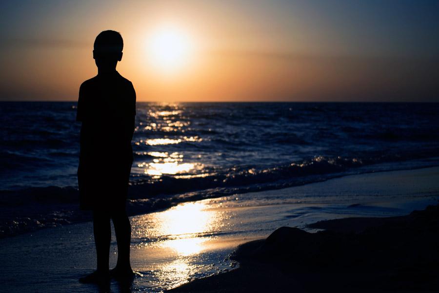 フリー写真 夕暮れのビーチと男の子のシルエット