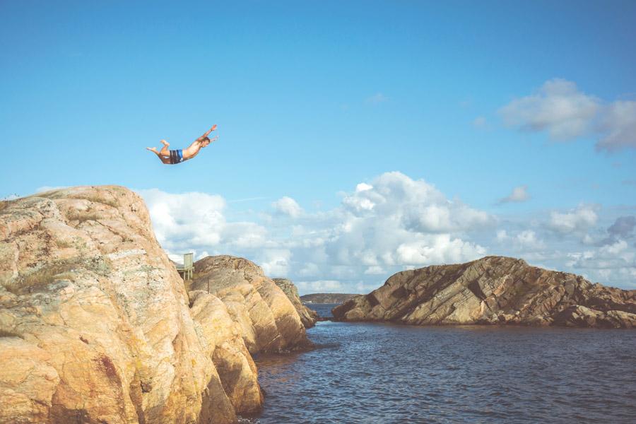 フリー写真 岩の上から海に飛び込む男性