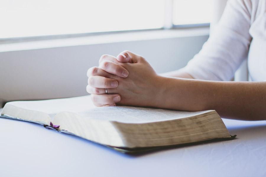フリー写真 聖書の上に手を置いて祈る人