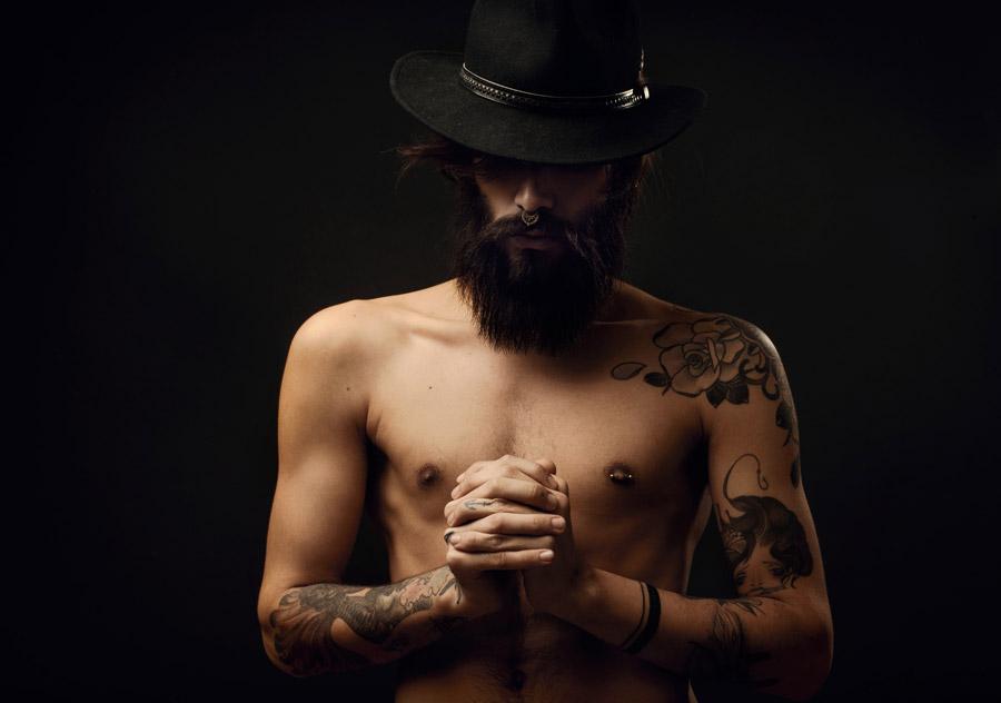 フリー写真 手を組んで祈りを捧げる刺青の男性