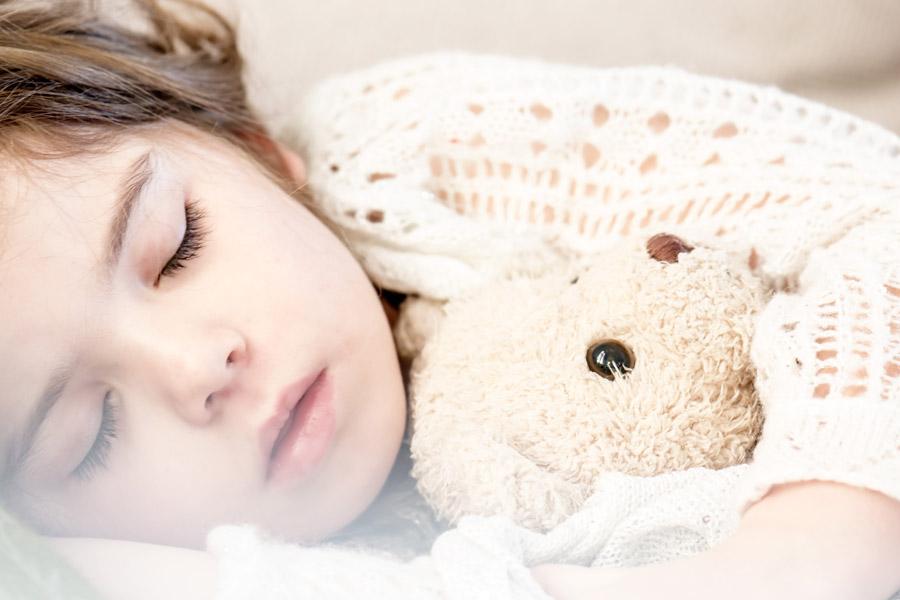 フリー写真 ぬいぐるみを抱いて寝ている外国の女の子