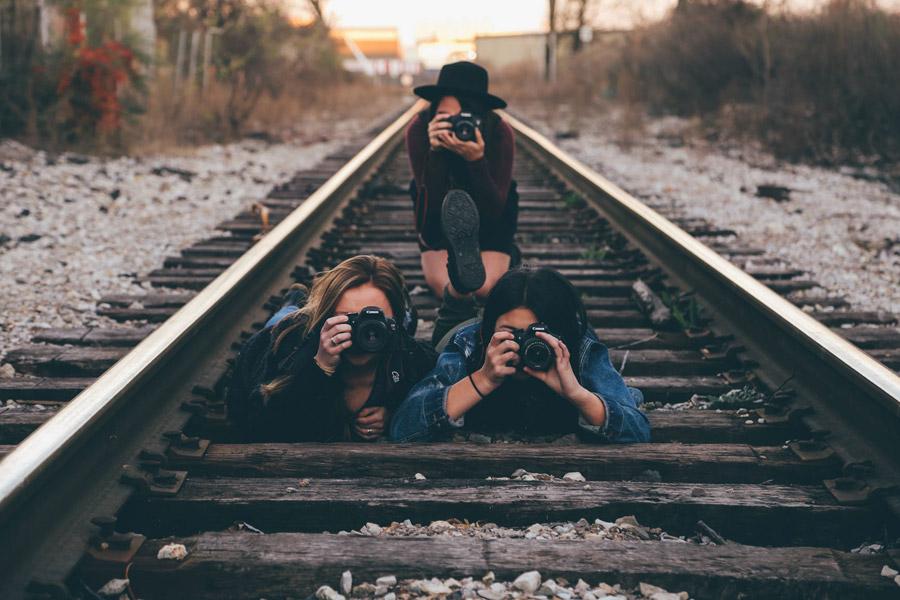 フリー写真 線路で写真を撮る三人の女性