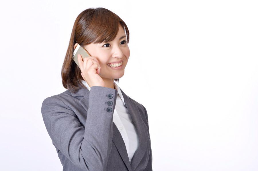 フリー写真 携帯電話で話し中の女性社員