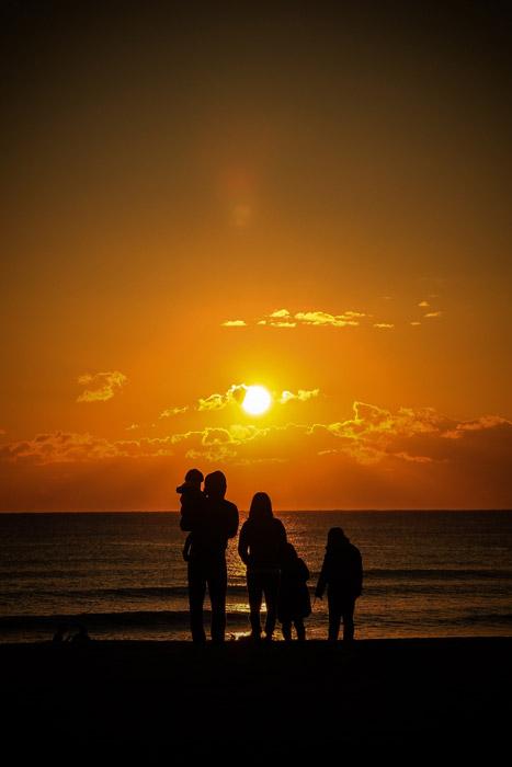 フリー写真 砂浜で夕日を眺める家族のシルエット