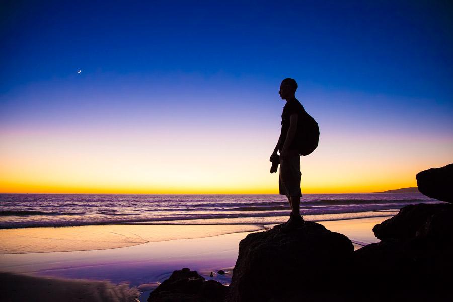 フリー写真 夕暮れの海と砂浜の岩に立つ男性のシルエット
