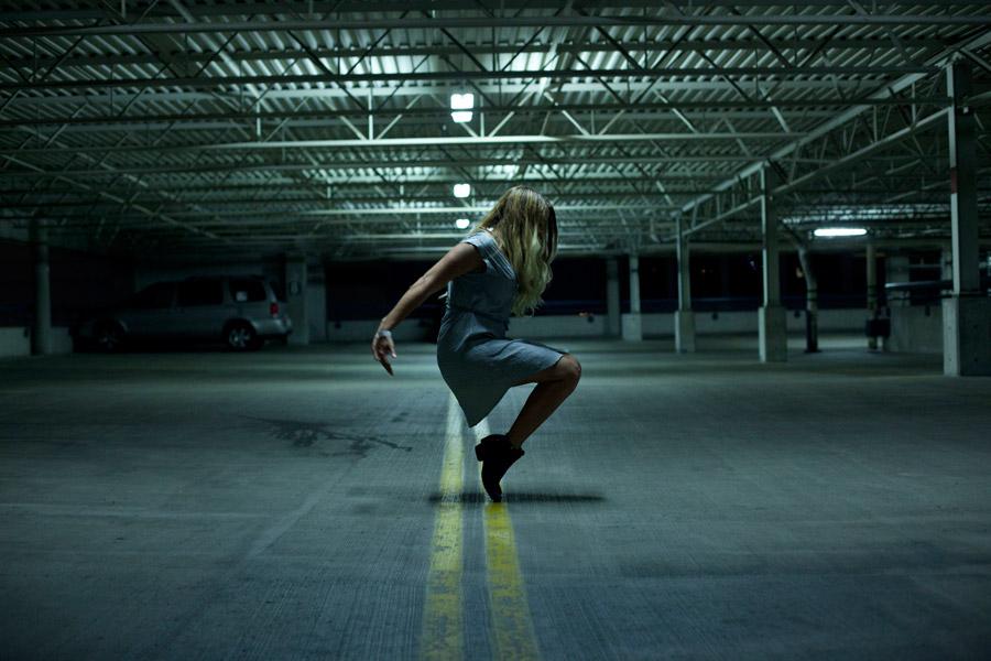 フリー写真 駐車場でつま先立ちする女性