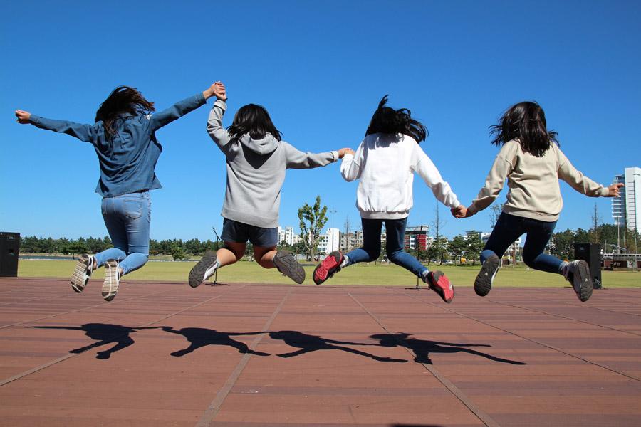 フリー写真 手をつないでジャンプする4人の女の子