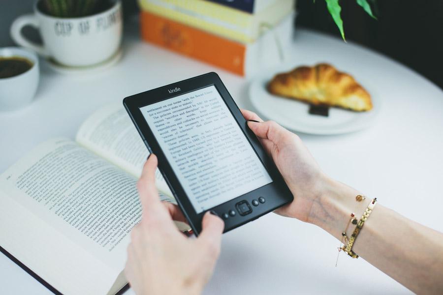フリー写真 電子ブックリーダーで電子書籍を読んでいる女性の手元