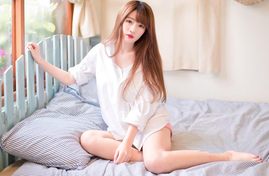 フリー写真 寝間着姿でベッドの上に座っている女性