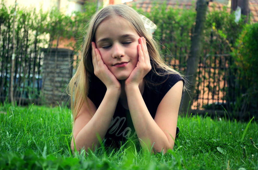 フリー写真 頬に手を当てて目を閉じている外国の少女