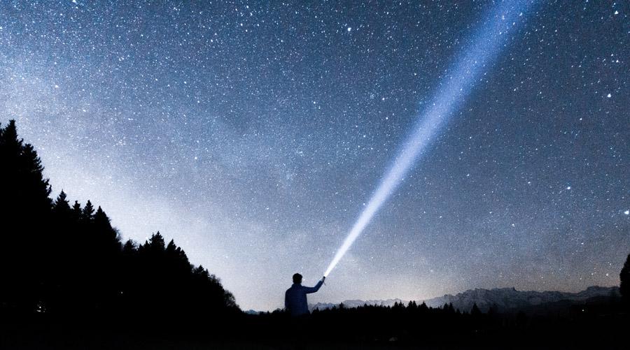 フリー写真 星空とライトを照らす人物