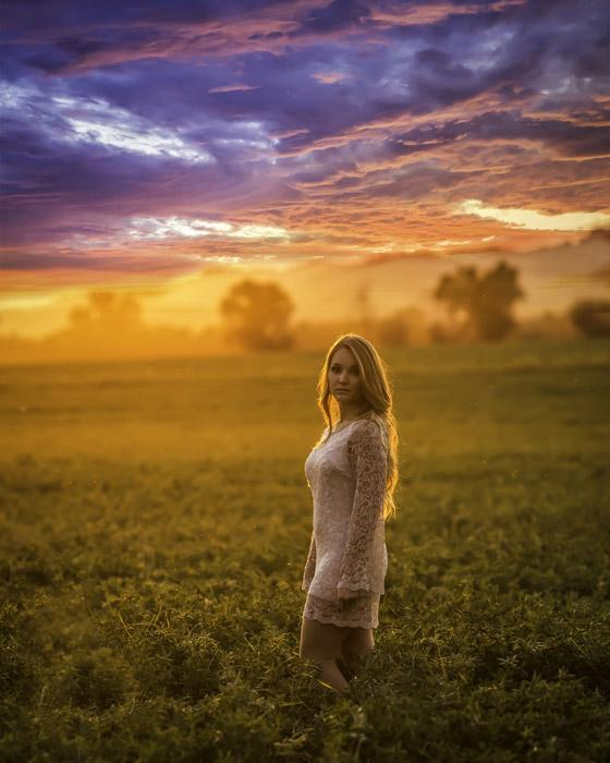 フリー写真 夕暮れの牧草地に立つ外国人女性