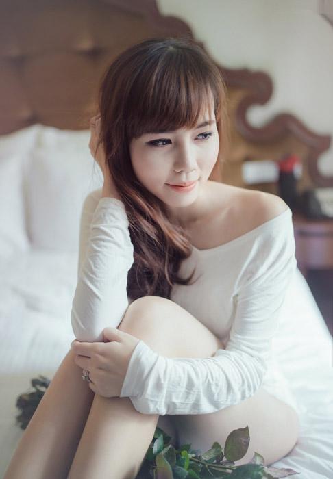 フリー写真 ベッドの上に座って髪の毛を押さえている女性