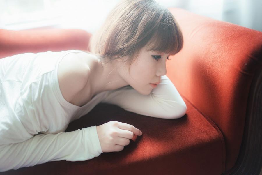 フリー写真 ソファーの上に寝転ぶ女性