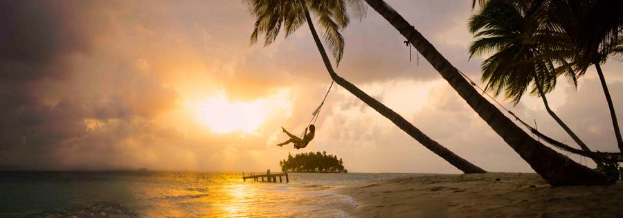 フリー写真 夕暮れのビーチでブランコに乗っている女性