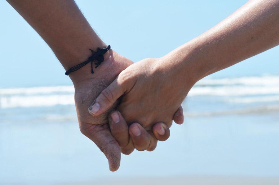 フリー写真 浜辺で手をつなぐカップルの手