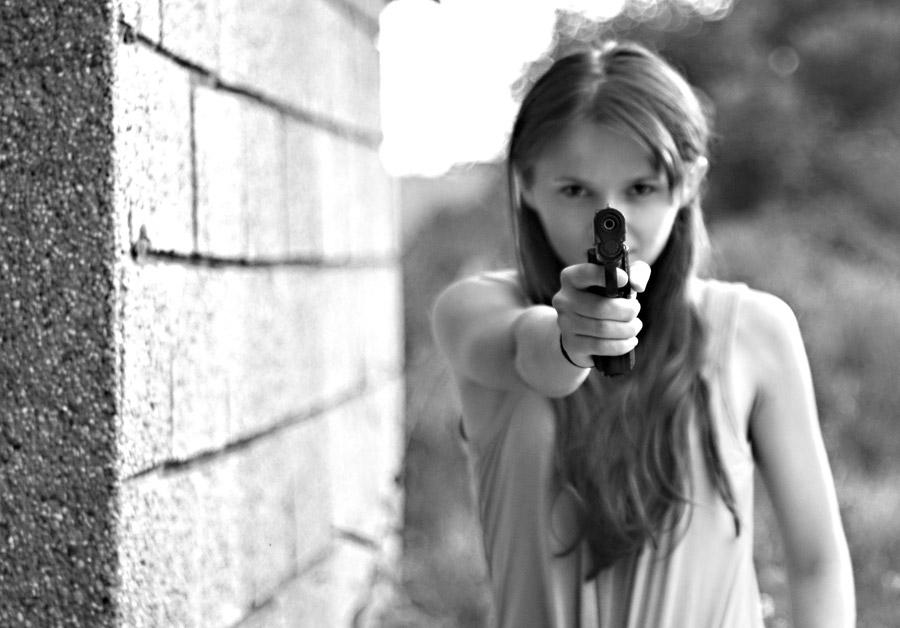 フリー写真 拳銃の銃口を向ける外国人女性