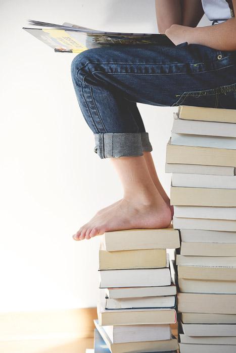 フリー写真 積み上げた本の上で本を読む人物
