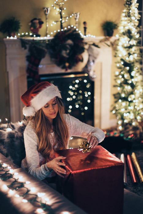 フリー写真 クリスマスプレゼントにリボンを付ける外国人女性