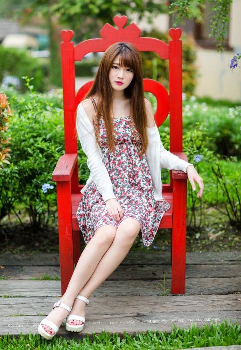 フリー写真 赤い椅子に座っている女性のポートレイト