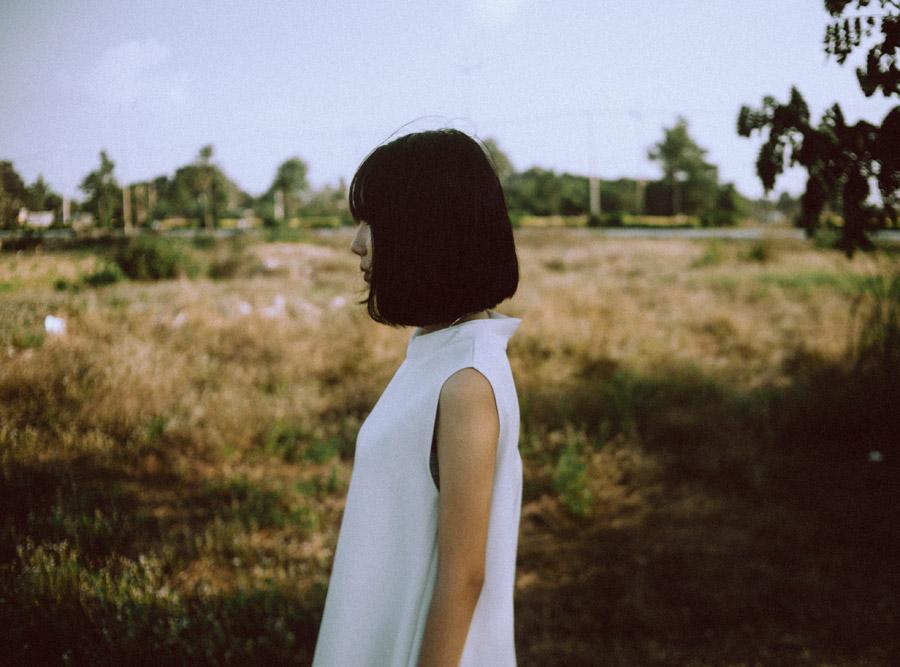 フリー写真 草むらで横を向いている女性