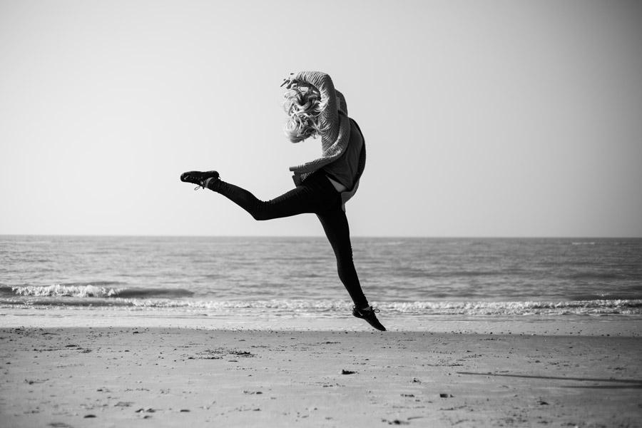 フリー写真 砂浜でジャンプする外国人女性