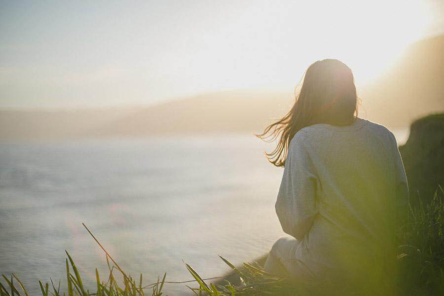 フリー写真 太陽の光と海を眺める女性の後ろ姿
