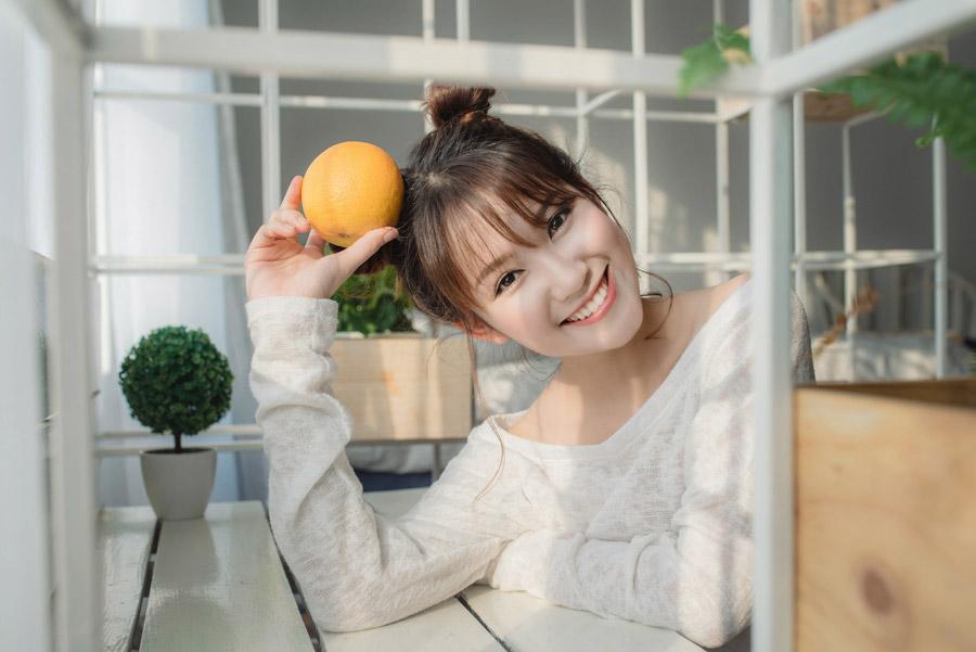 フリー写真 オレンジを頭に当てる女性