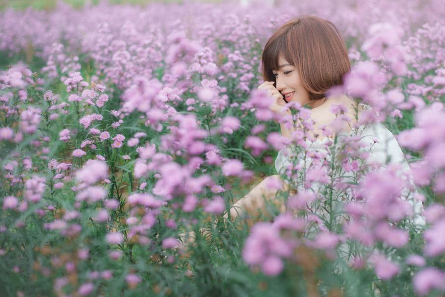 フリー写真 花畑の中で微笑んでいる女性