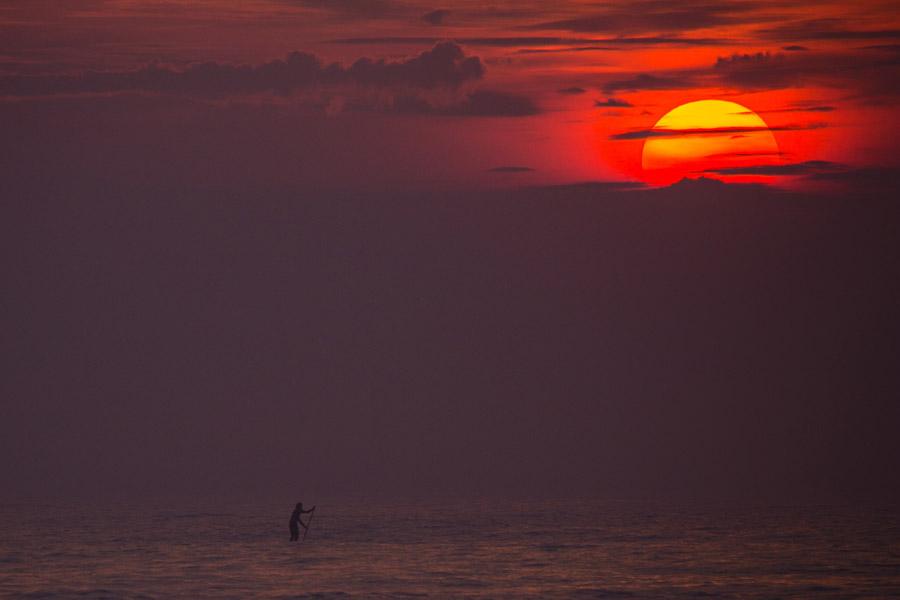 フリー写真 スタンドアップパドルをする人影と夕日の風景