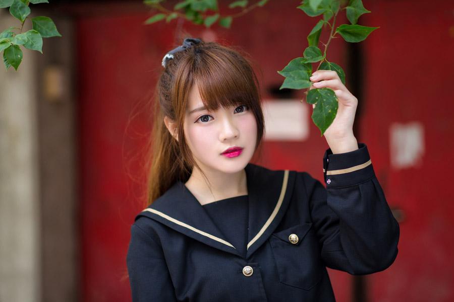 フリー写真 学生服姿で枝葉を持つ女子学生
