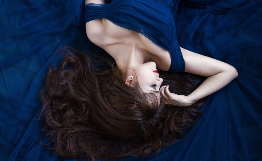 フリー写真 青いドレスの上で寝転ぶ女性