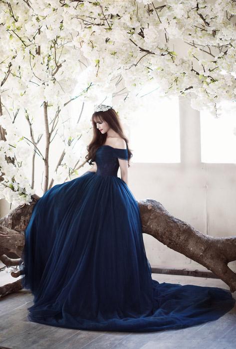 フリー写真 青いドレス姿で倒木の上に座る女性