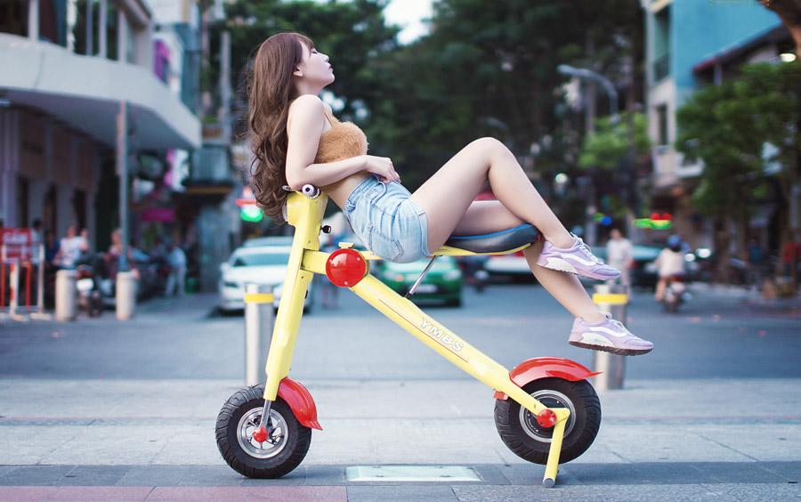 フリー写真 電動スクーターの上に腰掛けている女性
