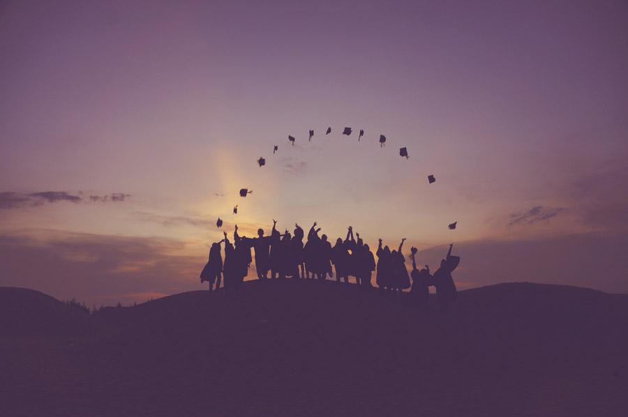 フリー写真 夕陽と帽子投げしている卒業生たち