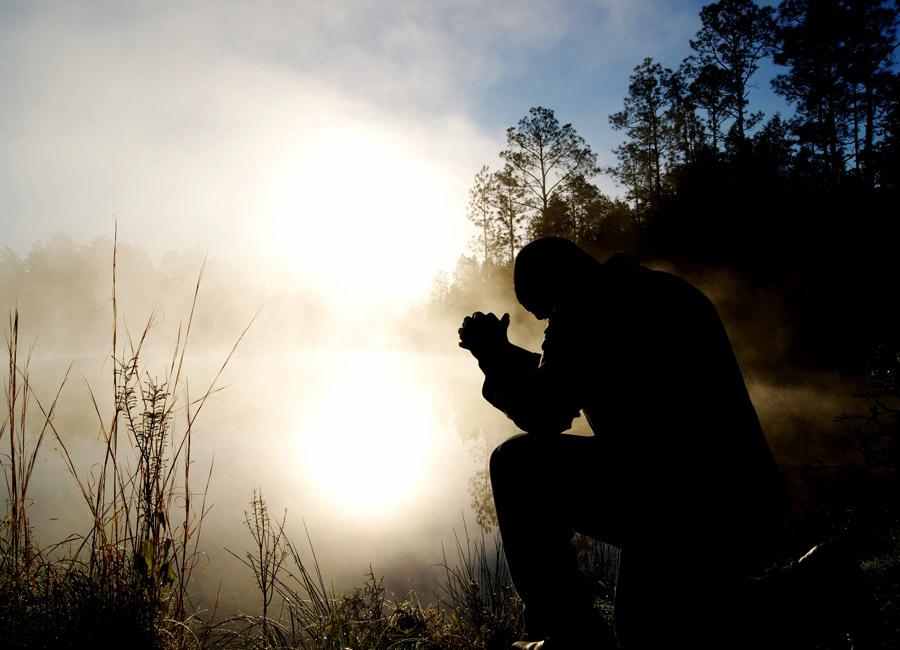 フリー写真 霧のかかる湖の前で祈りを捧げる人物
